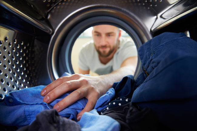 man taking clothes out of dryer